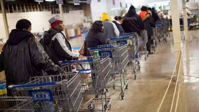 Menschen stehen mit Einkaufswagen in einer Schlange.
