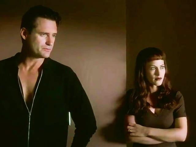Ein Mann und eine Frau stehen mit ernsten Blicken nebeneinander