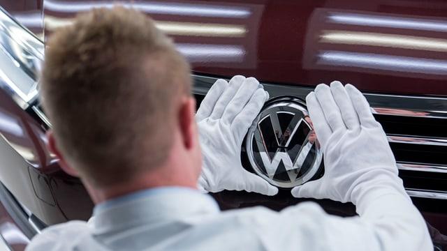 Ein VW-Mitarbeiter poliert das VW-Zeichen