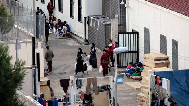 Menschen in einem Innenhof mit Gebäuden von Mauern umgeben.