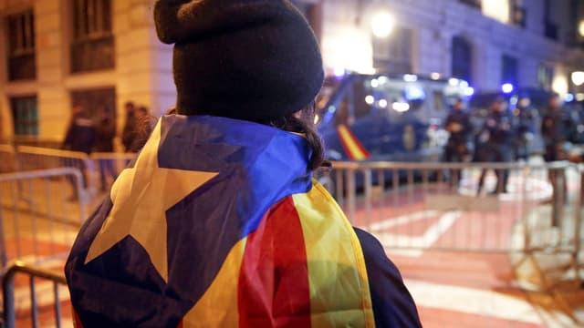 Symbolbild: Person mit katalanischer Flagge über den Schultern im Vordergrund (von hinten fotografiert), in der Ferne Polizisten.