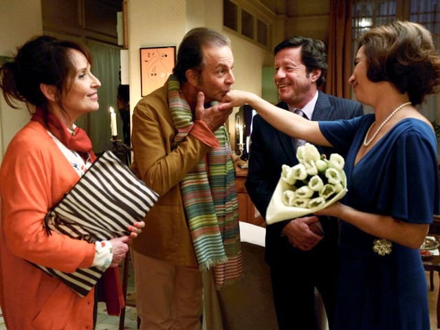 , Roland Giraud als Francis Caillaux küsst Rita Blanco als Maria Ribeiro die Hand, Chantal Lauby als Solange Caillaux und Joaquim de Almeida als José Ribeiro stehen dabei.