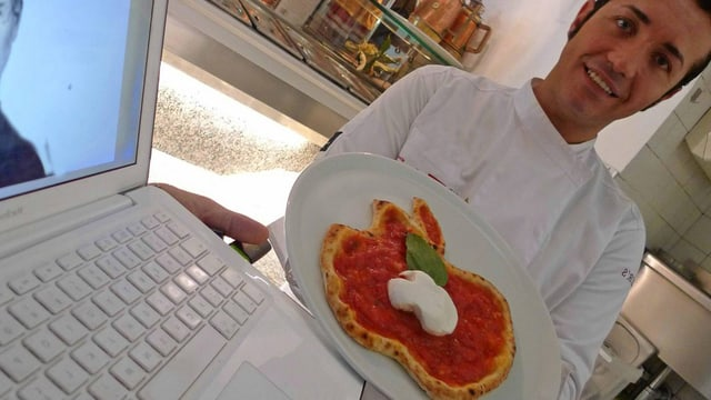Koch präsentiert stolz ein Pizza.