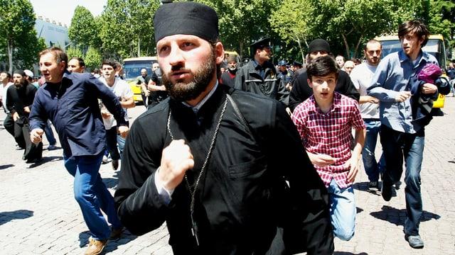 Georgisch-Orthodoxe Priester und Demonstranten gehen gewaltsam gegen Menschenrechtsaktivisten vor.