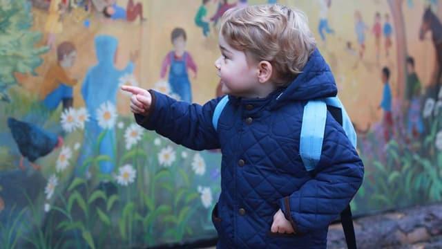 Prinz George mit blauer Jacke und hellblauem Rucksack.