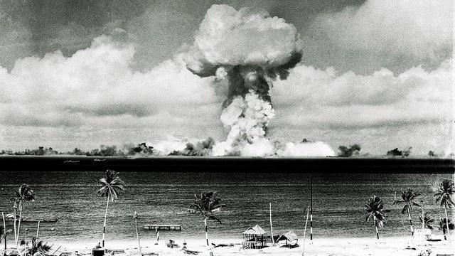 Ein Atompilz während eines Testzündung auf den Marshall-Islands 1946, im Vordergrund Palmen und Strand.