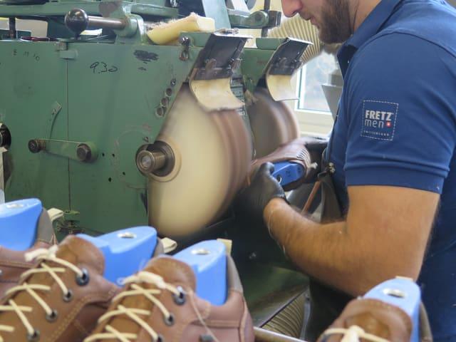 Arbeiter schleift Schuhsohle an Maschine
