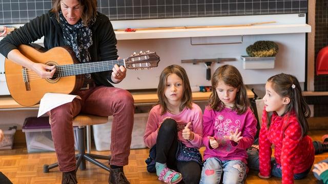 Eine Frau spielt auf der Gitarre, Kinder hören zu.