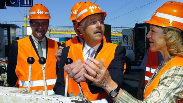 Drei Männer und eine Frau mit orangefarbenen Helmen stehen an Schalthebeln.