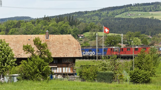 Ein Güterzug fährt in der Nähe von Bern an einem Bauernhaus vorbei. (keystone)