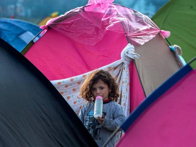 Mädchen mit Babyflasche zwischen Zelten.