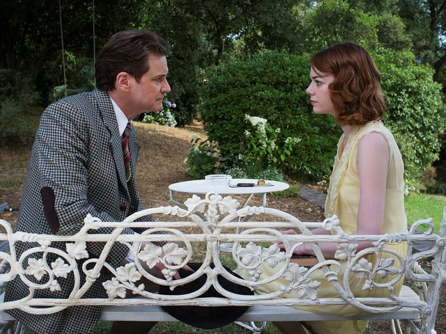 Colin Firth und Emma Stone schauen sich prüfend an. Zusammen sitzen sie an einem kleinen, weissen Tischchen in einem Park.