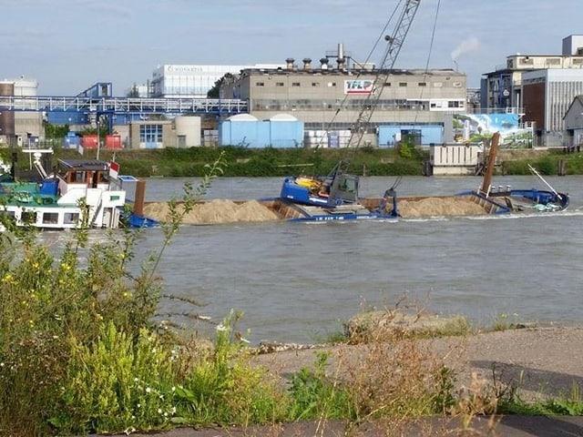 Ein schräg im Wasser liegendes Lastschiff