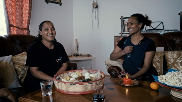 Zwei Frauen sitzen an einem Wohnzimmertisch