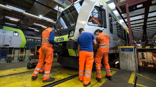 Drei Angestellte kontrollieren einen BLS-Zug