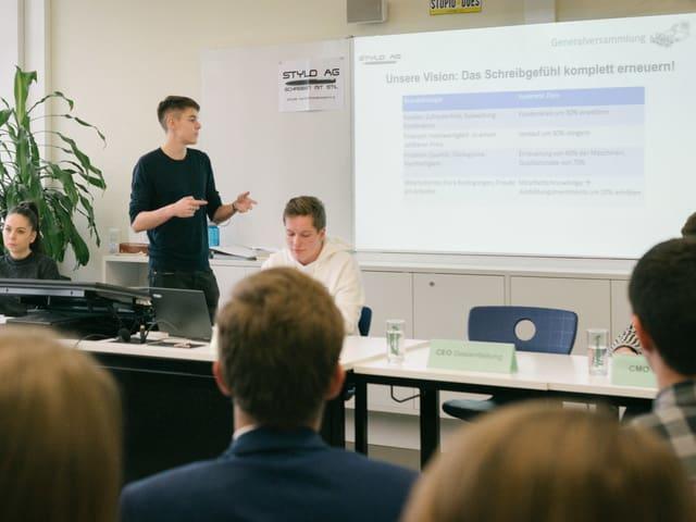 Schüler erklärt zur Präsentation auf Leinwand