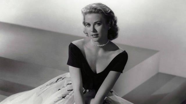 Eine schwarz-weiss Fotografie mit der jungen, blonden Grace Kelly in Pose auf einer Treppenstufe, in die Kamera blickend, gekleidet in einen Tüllrock, ein weit ausgeschnittes Oberteil und eine Perlenkette..