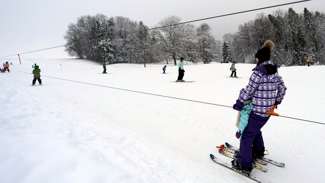 Frau lässt sich von kleinem Skilift hochziehen