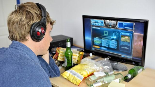 Jugendlicher mit Headset spielt am Computer.