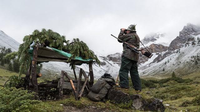 Jäger mit Feldstecher inmitten leicht verschneiter Berge