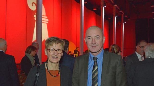 Die Baselbieter Regierungspräsidentin Sabine Pegoraro und ihr Regierungskollege Isaac Reber stehen vor der roten Wand mit dem weissen Basler Stab.
