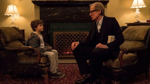 Bill Nighy sitzt auf einem Sessel. Neben ihm sitzt ein kleiner Junge auf einem Sessel.