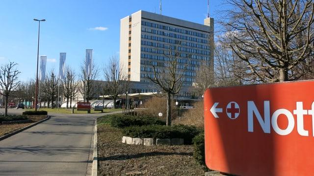 Bruderholzspital von aussen. Am rechten Bildrand sieht man ein grosses, rotes Schild, das den Weg zum Notfall weist.
