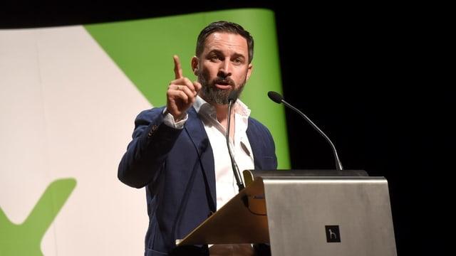 Der schwarzhaarige und baarttragende Abascal bei einer Rede am Rednerpult. Hinter ihm ein Plakat mit grünem Vox-Logo.