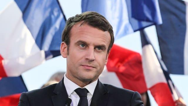 Ina fotografia d'Emmanuel Macron cun bandieras da la Frantscha davosvart.