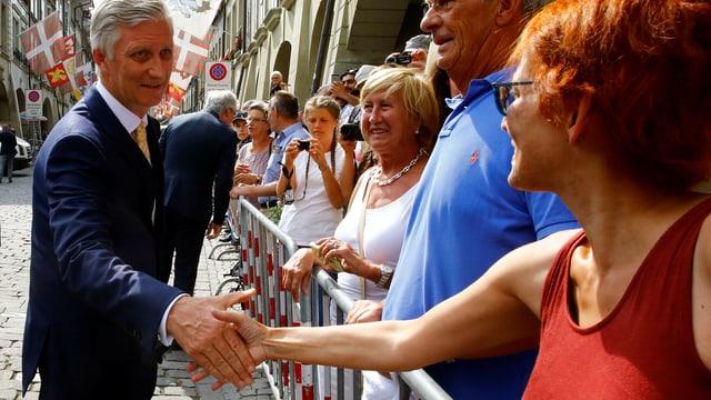 König Philippe schüttelt Hände von Zuschauer.