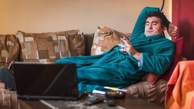 Ein Mann im Morgenmantel liegt auf dem Sofa, trinkt und schaut dabei in einen Laptop auf dem Sofatisch.