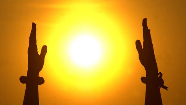 Zwei Hände reichen der Sonne entgegen.