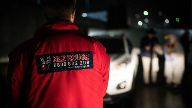Ein Mitarbeiter von Nez Rouge empfängt bei einem Auto eine Gruppe Kunden.