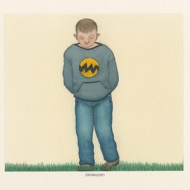 Ein Junge steht da und schaut auf den Boden.