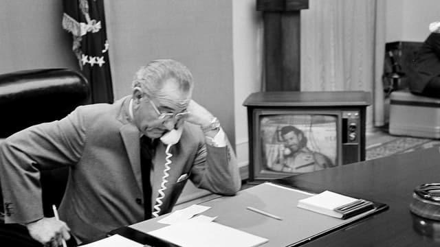 Lyndon B. Johnson telefoniert an seinem Schreibtisch.
