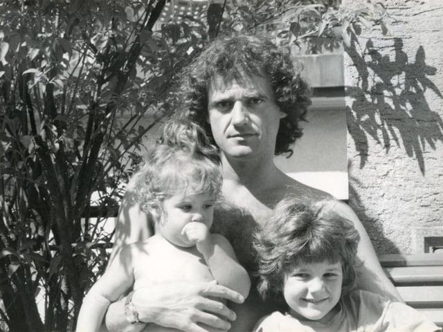 Ein Mann mit zwei kleinen Kindern auf dem Arm.