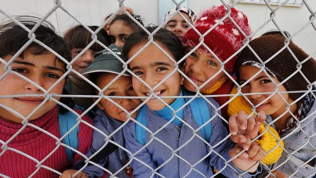 Syrische Flüchtlingskinder, lachend, hinter Maschendrahtzaun.