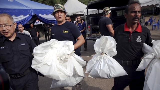 Forensiker tragen Säcke mit Leichenteilen weg