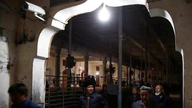 Mitglieder der uigurischen Minderheit in China laufen nach dem Verlassen einer Moschee an einer Überwachungskamera vorbei.