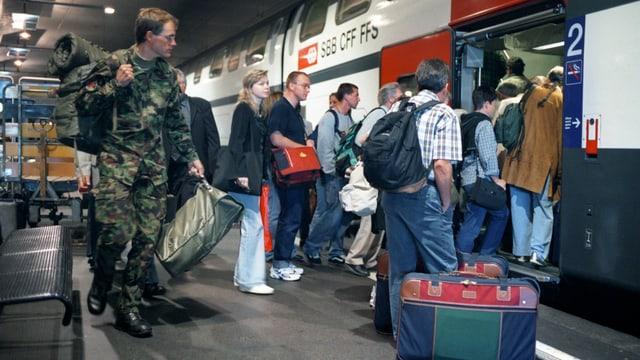 Passagiere drängen sich um eine Zugstüre.