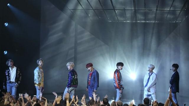 Sieben koreanische Sänger auf einer mit Scheinwerfern beleuchteten Bühne