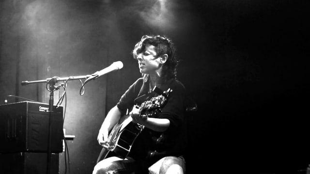 Schwarz-Weiss-Bild: Lisi mit Gitarre auf einer Bühne