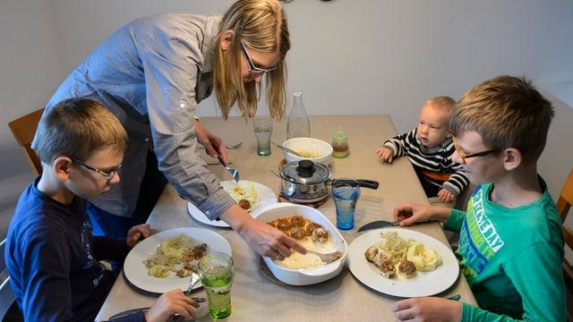 Familie mit drei Kindern beim Essen.