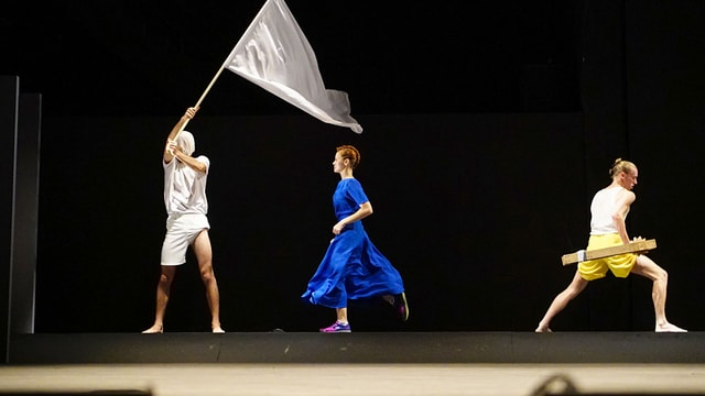 Drei Personen auf der Bühne. Eine mit einbandagiertem Kopf eine Fahne schwingend, eine Frau in einem leuchtend blauen Kleid und Turnschuhen, ein Mann trägt um die Hüften eine Holzkonstruktion.