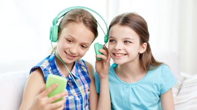 Zwei Mädchen hören einen Podcast