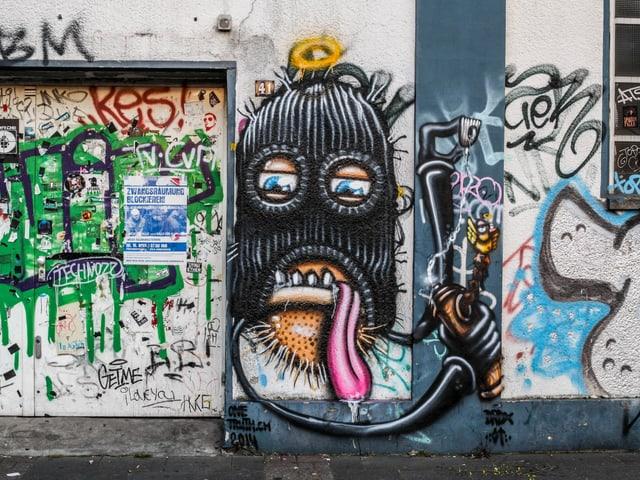 Ein Graffiti mit schwarzer Mütze auf einer Wand.