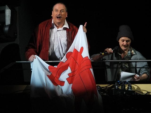 Mann auf dem Balkon entfaltet eine Baselbieter Fahne
