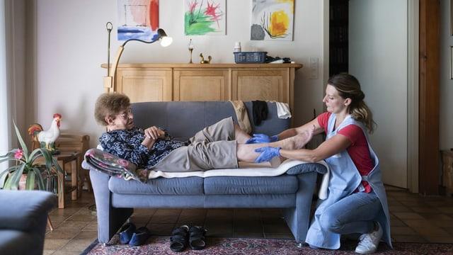 Spitex-Pflegefrau massiert das Bein einer Seniorin