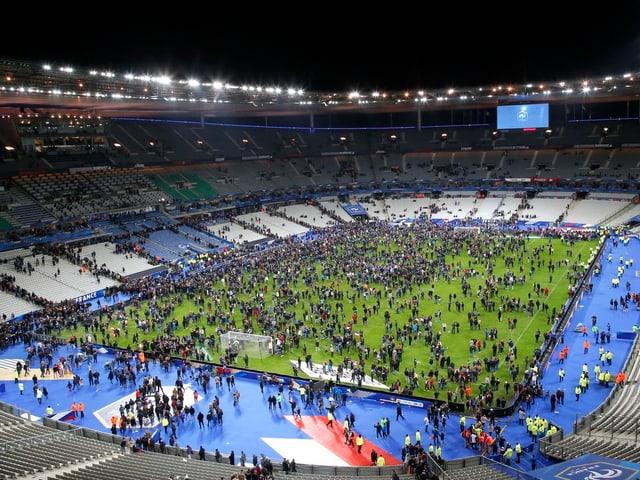 Hunderte Leute stehen auf dem grünen Spielfeld des Stadions. Die Ränge sind praktisch leer.