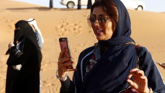 Symbolbild: Frau ohne Schleier mit Handy in der Wüste, dahinter Frau mit Schleier.